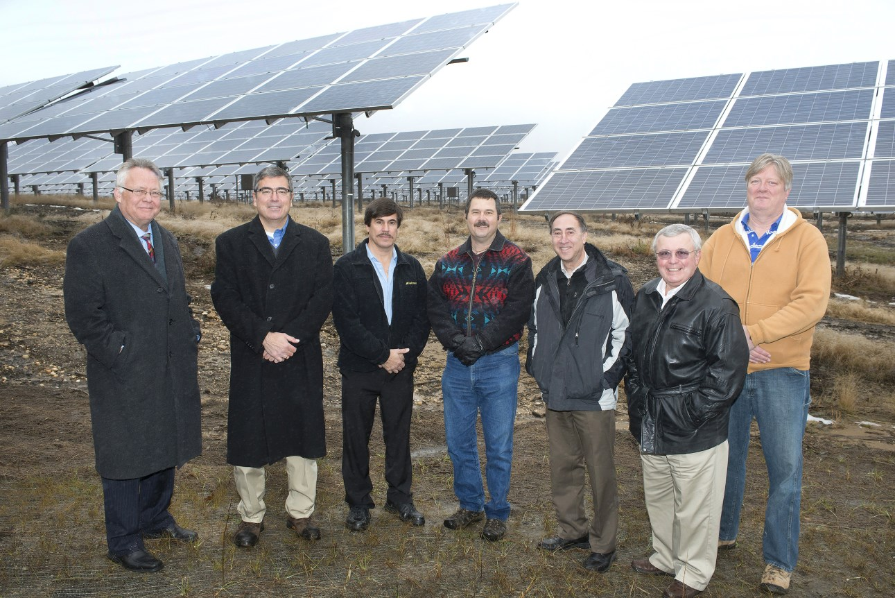 Photo of a group of seven men standing in a semi-circle in front of a field of large solar panels