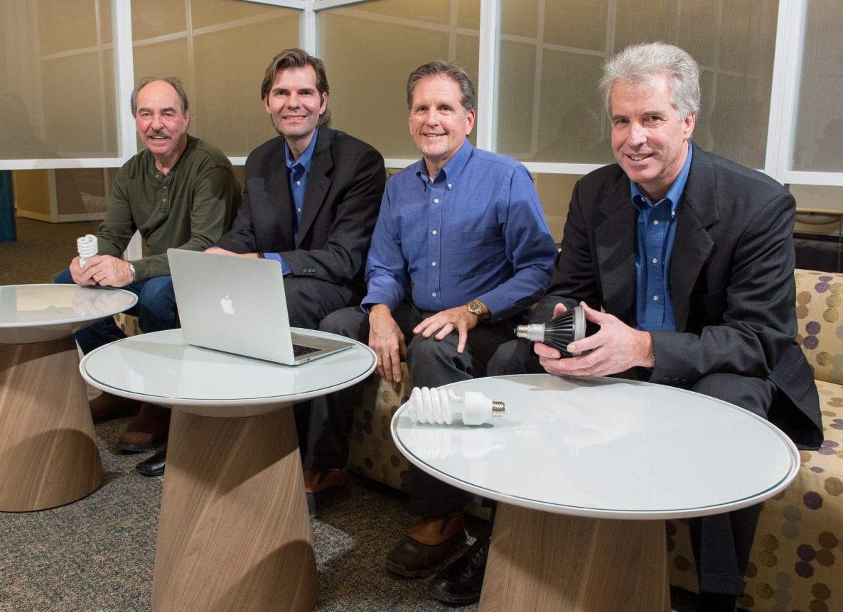 Four men sit behind three small tables; a lap top is on the table in front of the third man.