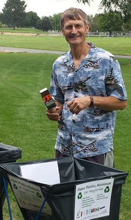 Photo of a man in a Hawaiian shirt stands over a recycling bin in park of green grass.