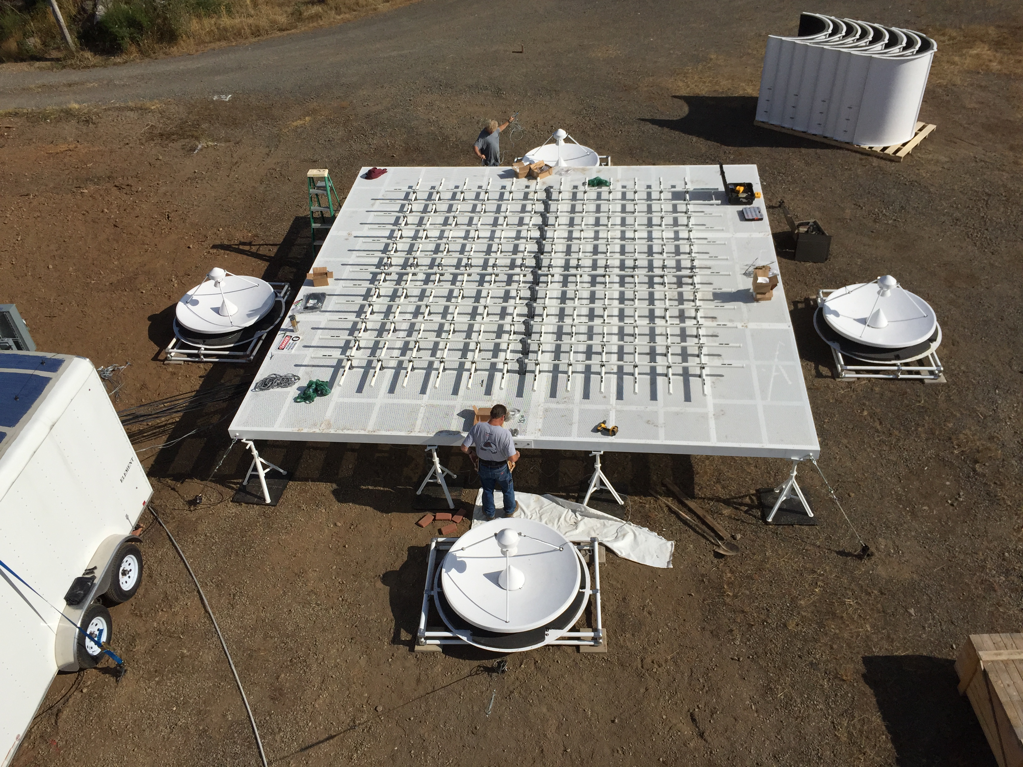 Photo of men working on a large square grid that has radar dishes on each of its four sides.]