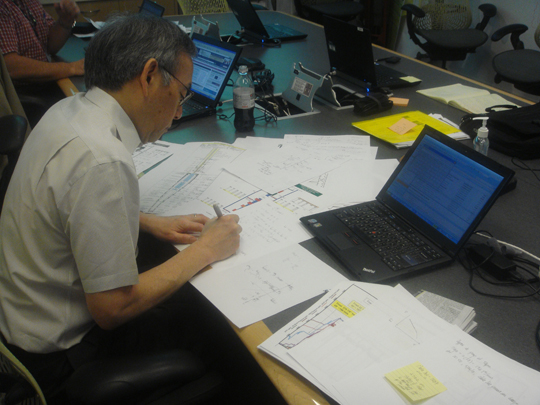 Secretary Steven Chu works on flow and resistance calculations on a conference room table