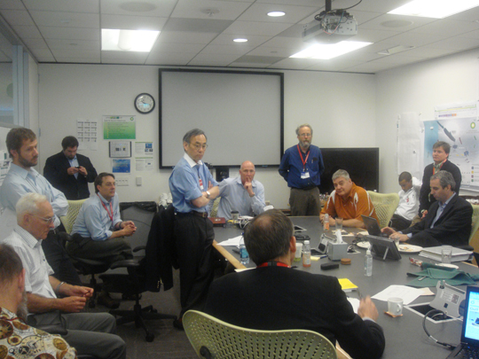 Secretary Steven Chu and National Laboratory scientists review options over a conference room table.