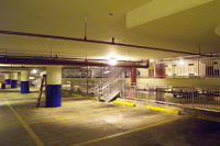 Photo of a parking garage interior with an LED ceiling light fixture at center.