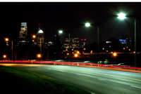 Photo of an urban road at night illuminated with roadway lights, with a city skyline in the background.
