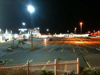 Photo of a shopping plaza showing an LED parking lot light to the left and an HPS light to the right.