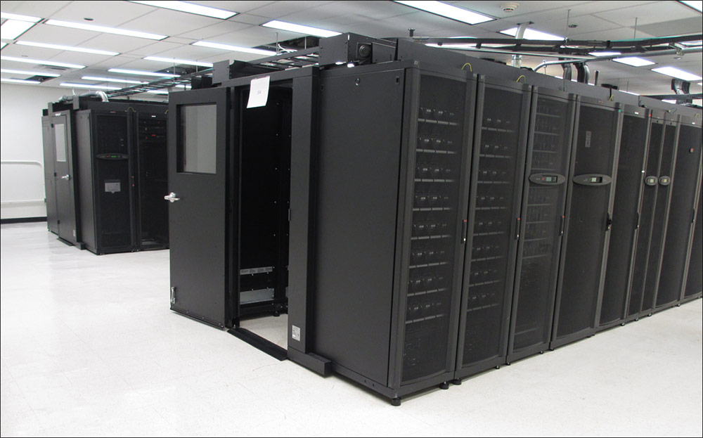 Photo of two long rows of black servers are situated in the middle of a data center that has white walls and a white suspended ceiling.