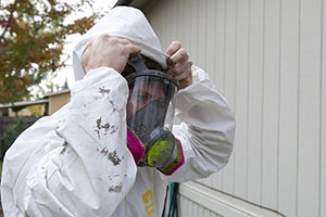Photo of a weatherization worker putting on personal protective equipment to prepare for adding insulation to this home.
