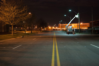 photo of a city street at night showing a maintenance crew checking a streetlight.