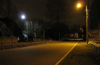 Photo of a residential street at night, with an LED street light at left and an HPS street light at right.
