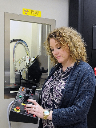 The Pantex Plant's Felicia Bellis uses controls to move a turntable of the microfocus X-ray machine, one of many technologies Pantex technicians use to ensure quality.