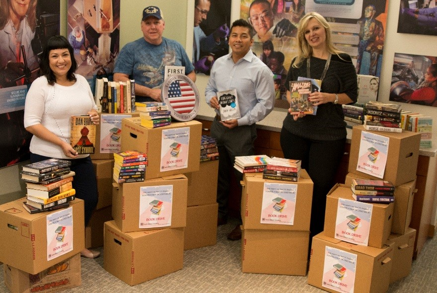 From left, Sandia/California Military Support Committee members Sarah Flores, Mark Cordes, Brian Abelgas, and Rachel Sowell pack up the 725 books collected for local veterans.