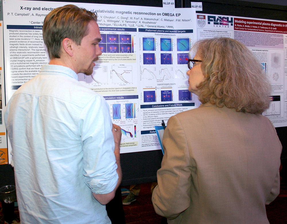 NLUF student Paul Campbell, University of Michigan, explains his poster on work at the OMEGA facility at the University of Rochester's Laboratory for Laser Energetics.