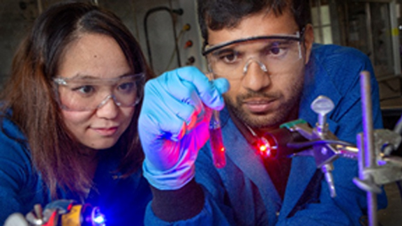 Researchers Yan Zhou (left) and Sahan Salpage (right) perform a photochemical separation of ruthenium and iron using blue and red light, respectively.