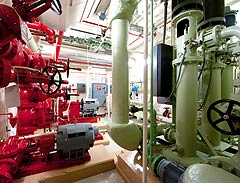 Photo of an equipment room in a high-rise commercial office building with red and green equipment.