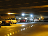 Photo at night of a parking garage filled with cars, with bright lights overhead.