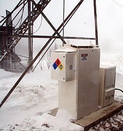 Photo of a fuel cell system in front of a radio tower with snow on the ground.
