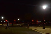 Photo of a street at night with a post-top street light in the right foreground and two more in the background.