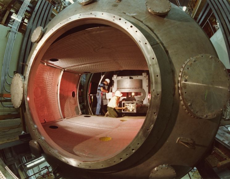 This 1978 photo shows two workers inside the Mirror Fusion Test Facility, a magnetic confinement fusion device designed and built at Lawrence Livermore National Laboratory. In this experiment, magnetic mirrors are placed at both ends of a central magnetic tube. Very hot and dense plasmas inside each mirror enhanced the confinement of another plasma inside the central tube, where the bulk of the fusion would occur. | Photo courtesy of Lawrence Livermore National Laboratory.