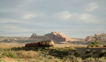 In the 1950s, one of the largest uranium deposits in the U.S. was found near Moab, Utah. The Department of Energy began cleaning up the uranium mill tailings from the Moab Site in April 2009, using steel containers to transport more than five million tons of tailings for safe disposal near Crescent Junction, Utah. In this May 2012 photo, one of the trains is shown on the Union Pacific Railroad in Utah, passing a butte capped by a familiar southwest U.S. rock formation known as Navajo Sandstone. | Photo courtesy of the Department of Energy.