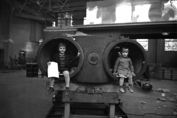 """In this 1939 photo, Eric and Margaret Lawrence are sitting inside the tank of something called the 60-inch cyclotron -- a machine invented by their father, Ernest Lawrence. The cyclotron is a unique circular particle accelerator, which Lawrence himself referred to as a """"proton merry-go-round."""" In reality, the cyclotron specialized in smashing atoms. Fun facts: this cyclotron contains a magnet that weighs 220 tons, and experiments conducted on this very machine led to the discovery of plutonium and Nobel Prizes for researchers Glenn Seaborg and Melvin Calvin. Ernest Lawrence passed away in 1958 -- just 23 days later, the Regents of the University of California voted to rename two of the university's nuclear research sites: Lawrence Livermore and Lawrence Berkeley Laboratories. 