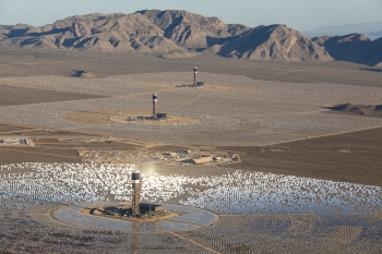 Located in the Mojave Desert, 40 miles southwest of Las Vegas, the Ivanpah Solar Electric Generating System is the largest solar thermal energy facility in the world, with 392 MW of capacity – meaning it can produce enough renewable electricity to power nearly 100,000 homes. It uses 173,500 heliostat mirrors spread over approximately 3,500 acres, focusing solar energy on boilers located atop three solar power towers, generating steam to turn a conventional steam turbine. The facility is owned by NRG Solar, Google and BrightSource Energy. The Energy Department provided a $1.6 billion loan guarantee to the project. Pictured here is an aerial perspective of the nearly completed Ivanpah Solar Power Facility, taken in April 2013.   Photo courtesy of Gilles Mingasson/Getty Images for Bechtel.