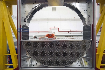 On June 6, 2013, researchers at Jefferson Lab completed the construction of the Forward Calorimeter in Hall D. The calorimeter was built to measure the energy of particles as they are created inside the target area and strike against lead glass blocks that make up the calorimeter. Upon striking the calorimeter, the particles will create a shower of light, which will then be digitized and used to measure energy of particles. In this photo, John Leckey, a postdoctoral researcher from Indiana University, is assembling the Forward Calorimeter in Jefferson Lab's newest experimental area, Hall D. Leckey helped assemble the calorimeter along with Manuel Lara and Daniel Bennett, postgraduate students from Indiana University. The calorimeter contains 2,800 lead glass blocks. | Photo courtesy of Jefferson National Laboratory.