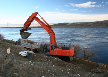 An excavator scoops out a section of river outfall pipeline at an F Area waste site. The pipeline was used to discharge effluent into the Columbia River.