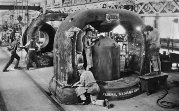 """The cyclotron, invented by Ernest Lawrence in the 1930s, is a unique circular particle accelerator, which Lawrence himself referred to as a """"proton merry-go-round."""" In reality, the cyclotron specialized in smashing atoms. Part of this atom-smashing process requires very large, very heavy magnets -- sometimes weighing up to 220 tons. In this photo, workers at the Federal Telegraph facility in Menlo Park, California, are smoothing two castings for 80-ton magnets for use in one of Lawrence's cyclotrons at the University of California, Berkeley. Lawrence passed away in 1958 -- and just 23 days later, the Regents of the University of California voted to rename two of the university's nuclear research sites: Lawrence Livermore and Lawrence Berkeley Laboratories. 