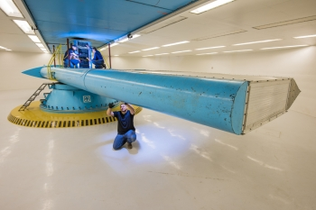Sandia National Laboratories are home to the state-of-the-art Centrifuge Test Complex, with both indoor and outdoor centrifuges designed to simulate environments and situations with high inertial forces, like atmospheric reentry and jet aircraft acceleration. This photo shows the 29-foot-radius indoor centrifuge that's housed in an underground, temperature-controlled environment. The centrifuge can accelerate a maximum payload of 16,000 pounds to 100 Gs, or lighter loads to 300 Gs, allowing researchers to develop satellite and rocket components, geotechnical loads and sensing devices, to name a few. Pictured here, Glenn Yarborough inspects the centrifuge arm while Orlando Abeyta (left) and Ed Romero (right) work above. Photo by Randy Montoya, Sandia National Laboratories.