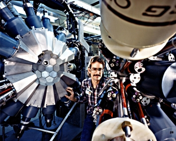 What in the world is happening in this photo?  The person pictured here is an Oak Ridge National Laboratory technician, making adjustments to a particle accelerator, part of the Holifield Heavy Ion Research Facility (HHIRF) in Oak Ridge, Tennessee. This photo was taken in January 1987.  HHIRF's last experimental run was in 1992, but during its decade of operation, it set the stage for a wide range of scientific research experiments at Oak Ridge National Lab. By accelerating intense beams of light ions to strike a target, the facility creates short-lived, radioactive nuclei that are used for astrophysics research. Fun fact: The nuclei exist for just about one-billionth of a second. | Photo courtesy of Oak Ridge National Laboratory.