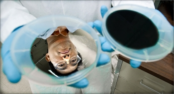 A silver wafer reflects the face of NREL research scientist Hao-Chih Yuan, before the wafer is washed with a mix of acids. The acids etch holes, absorbing light and turning the wafer black. | Photo Credit: Dennis Schroeder, NREL