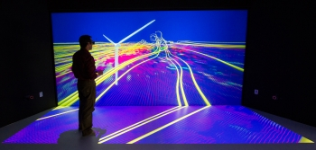 """At the National Renewables Energy Laboratory (NREL), scientists use the Insight Center Collaboration Room to examine and interact with their data. In this simulation, the room is converted into a virtual wind tunnel, allowing scientists to study the complex, turbulent flow fields around wind turbines. Pictured here, NREL Senior Scientist Kenny Gruchalla examines the velocity field surrounding a wind turbine, using a 3-D model projected onto the center's 16-by-8 foot wall. The simulation helps scientists better understand flow patterns, and further, how turbines can better avoid gearbox failures. <a href=""""http://www.nrel.gov/news/features/feature_detail.cfm/feature_id=2254"""" target=""""_blank"""">Learn more about the Insight Center Collaboration Room</a>. 