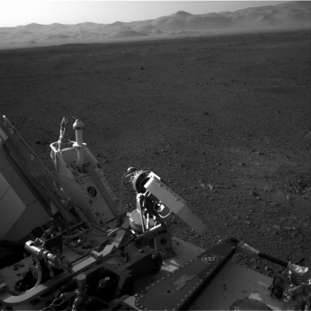 """On Monday, August 6, 2012, NASA's Curiosity rover arrived on the surface of Mars to gather geological and environmental data to determine if the planet has ever had the potential to support life. This photo was taken by a navigation camera located toward the back-left of the Curiosity rover, and features part of the rover's nuclear <a href=""""/node/381709"""" target=""""_blank"""">power supply</a>. Beyond the rover itself, Curiosity's exploration reveals the desert-like terrain of Mars's Gale Crater. 