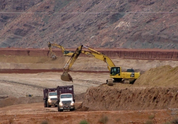 Empty containers on haul trucks are loaded with mill tailings.