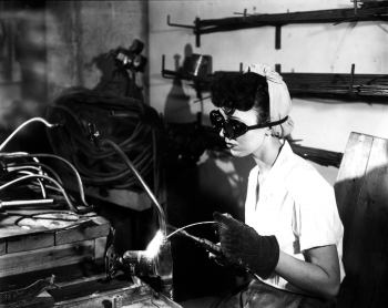 """James Edward Westcott was one of the only people permitted to have a camera at the Oak Ridge site during the Manhattan Project and the Cold War. He documented the lives of many of the residents and workers in the """"Atomic City,"""" in the days before Oak Ridge National Laboratory was actually Oak Ridge National Lab. In this February 1945 photo, a young woman is welding in the prefabrication shop building, part of the K-25 uranium separation facilities, one of three Manhattan Project sites in Oak Ridge, Tennessee. Many of the men and women who worked on these projects still live in Oak Ridge, Tennessee, today.   Photo by James Edward Westcott, courtesy of DOE & the National Archives."""
