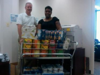 Barry Gaffney and Evette Dillon with EM's Office of Program Planning and Budget stand behind a portion of the office's donations to Feds Feed Families.