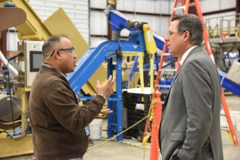 Idaho National Laboratory (INL) Director Mark Peters (right) talks with INL researcher Jaya Tumuluru, whose DOE Lab-Corps project is a high moisture pelleting process for the raw biomass material that feeds biofuel refineries. Image: Idaho National Laboratory.