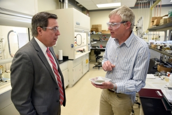 Idaho National Laboratory (INL) Director Mark Peters talks with INL research lead Tedd Lister whose Lab-Corps project is working to retrieve critical and rare earth materials from devices such as computers and cell phones. Image: Idaho National Laboratory.
