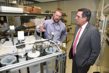 Idaho National Laboratory (INL) Director Mark Peters (right) talks with INL researcher Aaron Wilson, whose DOE Lab-Corps project is a water treatment process with the potential to cost-effectively recover clean water from dirty, salty, industrial wastewater. Image: Idaho National Laboratory.