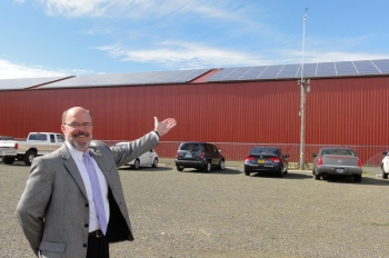Bob Repine, Oregon Department of Energy director, presents the Benton County Fairgrounds solar barn built with American Recovery and Reinvestment Act funds. The rooftop solar array will produce nearly a quarter of the energy used at the fairgrounds and the 12,000-square-foot space will house livestock and the Solar Education Center. | Photo courtesy of the Oregon Department of Energy