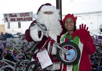 An elf from DOE's Savannah River Site poses with Santa Claus, who holds a bike, one of the more than 14,200 toys federal employees and contractors donated to the U.S. Marine Toys for Tots Program. Mounds of bikes and other donated toys for the program can be seen in the background.