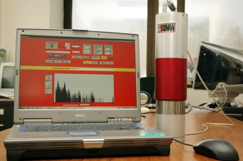 The simple, portable device identifies materials through their characteristic energy signals as unique as fingerprints. The three detectors are housed in a thermos-sized container that is connected to a laptop computer. The device issues a signal turning the laptop display bright red when nuclear material of interest is identified. | Photo courtesy of Princeton University