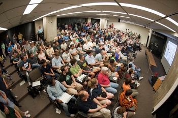 """More than 200 Fermilab researchers and staffers crowded into an auditorium at 2 a.m. EDT July 4 and waited for the latest announcement regarding the Higgs boson. When CERN Director-General Rolf-Dieter Heuer said the words - """"I think we have it"""" – the Fermilab crowd erupted into applause. Fermi National Accelerator Laboratory and Brookhaven National Laboratory are the host laboratories for the U.S. contingents of the Large Hadron Collider (LHC) experiments that found the Higgs boson-like particle. They and researchers from Argonne National Laboratory, Lawrence Berkeley National Laboratory and SLAC National Accelerator Laboratory are among the 1,700 scientists, engineers, technicians and graduate students from the United States that helped design, build and operate the LHC accelerator and particle detectors, and analyze the data from the collisions. Read the story: <a href=""""http://energy.gov/articles/last-piece-puzzle-celebrating-higgs-boson"""">The Last Piece of the Puzzle: Celebrating the Higgs Boson</a> 