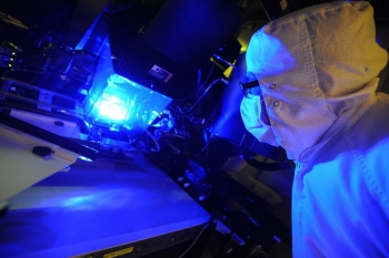 Solar Junction, in partnership with NREL, has developed solar cells that reach a record-breaking 44 percent efficiency -- meaning that more than 40 percent of the sunlight the solar cells are exposed to is converted into electrical energy. In this photo, an operator inspects a photolithography tool used to manufacture these solar cells. | Photo by Daniel Derkacs/SolarJunction.