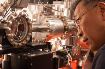 SLAC staff scientist Yiping Feng examines a chamber at LCLS' Front End Enclosure, where a thin crystal spectrometer is installed to measure the shot-by-shot characteristics of X-ray laser pulses. | SLAC National Accelerator Photo by Matt Beardsley