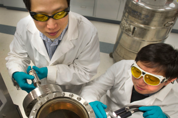 Brookhaven physicists Weidong Si (left) and Qiang Li look into the vacuum chamber where the new high-field iron-based superconductors are made through a process called pulsed-laser deposition.