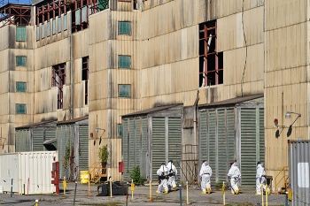 Workers enter Building K-27 to prepare the facility for demolition.