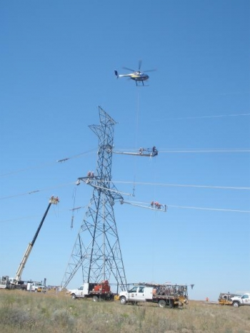 A helicopter hoists platforms for linemen during the construction of this single-circuit 500-kilovolt tower – one of hundreds on the McNary-John Day line saving BPA big bucks. | Photo courtesy of Bonneville Power Administration
