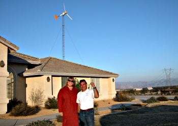 Homeowner Andrea Mitchel, with installer Joe Guasti, proudly shows off small wind turbine installed in Oak Hills, CA.   Photo by Karin Sinclair, National Renewable Energy Laboratory.