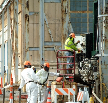 Workers drill holes for installation of electrodes as part of a heating system to help clean up contamination.